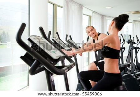 Athletic couple on veloargometers in gym, having fun