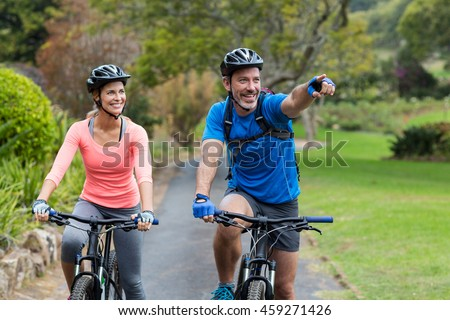 Athletic couple pointing while riding bicycle on the road