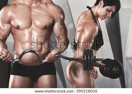 Athletic couple poses. Bodybuilders. - stock photo