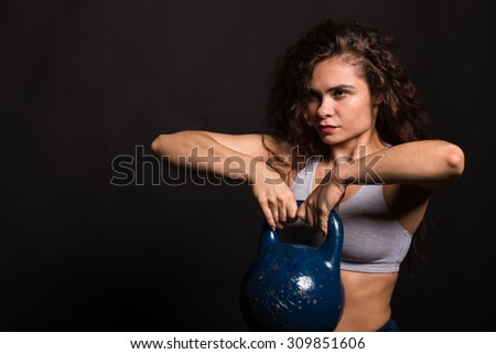 Athletic girl on a black background. Curly girl. Sport, health, women's fitness.
