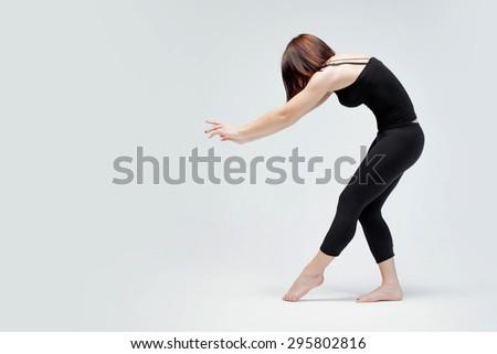 athletic girl on white background, pushing something  - stock photo