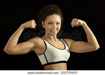 Athletic girl shows biceps - stock photo
