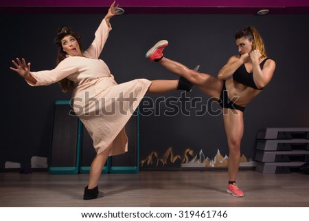 Athletic girl struggling with fat women. Same model  - stock photo