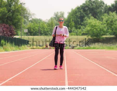 Athletic girl walking red sport running tracks. Casual sport clothes.