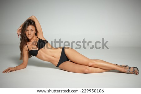 athletic girl with beautiful healthy skin in black lingerie lying on its side on a white background - stock photo