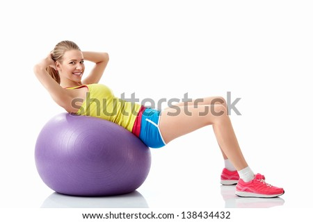 Athletic girl with fitball on white background