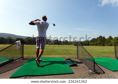 Athletic golfer swinging at the driving range dressed in casual attire. - stock photo