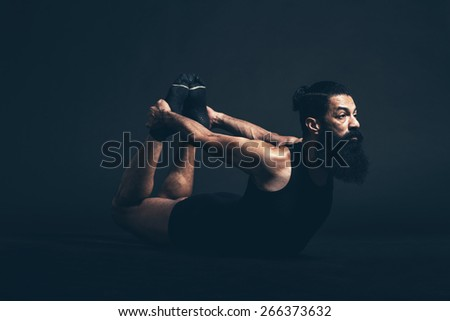 Athletic Guy with Long Beard and Mustache Doing Dhanurasana Bow Yoga Pose While Facing to the Right on a Black Background. - stock photo