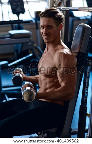 athletic guy workout with dumbbells, perfect shoulders, biceps, triceps and chest. Handsome power athletic man in training pumping up muscles with dumbbells in a gym. - stock photo