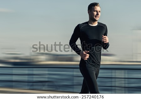 Athletic Handsome Man in Black Workout Clothing Running at the River Bridge Early in the Morning. - stock photo
