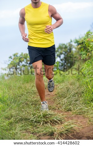 Athletic legs of fit runner man training cardio workout on trail mud grass path in summer nature mountains. Sports man lower body crop for thighs and knees concept wearing shorts and running shoes.