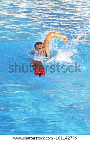 Athletic lifeguard in swimming pool - stock photo