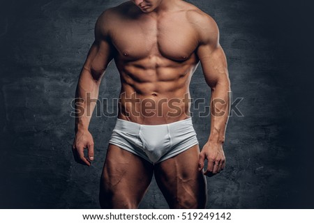Athletic male body in white panties on grey vignette background.
