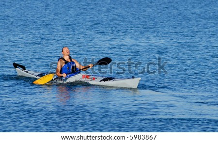 Athletic male kayaker emerges on the surface after paddle float assisted re-entry and roll. - stock photo