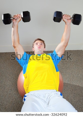 Athletic Male Lifting Weights in Gym Sitting On Medicine Ball - stock photo