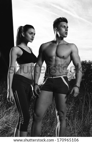 Athletic man and woman after fitness exercise .B&W photo