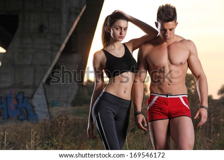 Athletic man and woman at sunset - stock photo