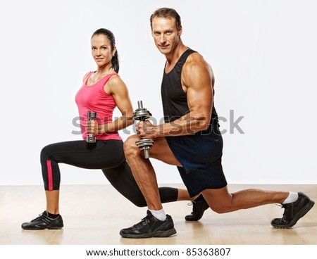 Athletic man and woman with a dumbells. - stock photo