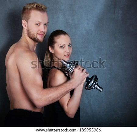 Athletic man and woman with a dumbells near the wall