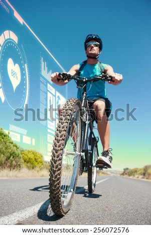 Athletic man cycling on open road against fitness interface - stock photo