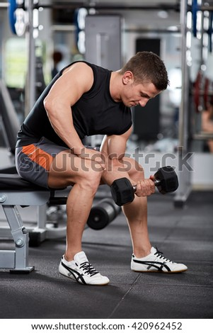 Athletic man doing biceps curl in seated position in the gym