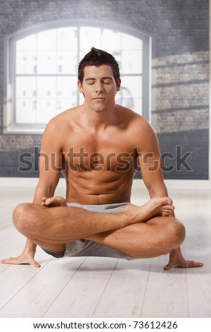 Athletic man doing exercise in lotus posture on floor with eyes closed.? - stock photo
