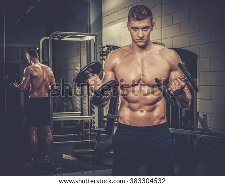 Athletic man doing exercises with dumbbells in The Gym's Studio - stock photo