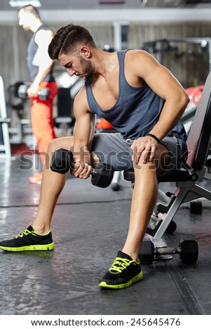 Athletic man doing fitness workout with dumbbell in a gym - stock photo