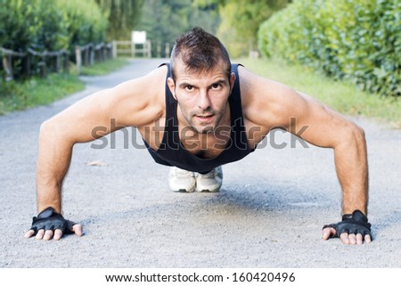 Athletic man doing push up outdoor. - stock photo