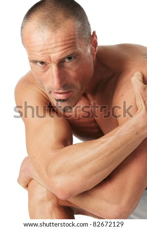 Athletic man in a squatting position, studio shot against a white background.
