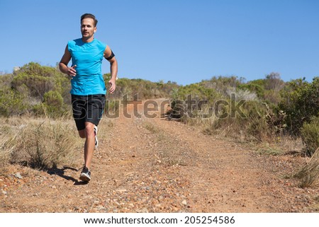 Athletic man jogging on country trail on a sunny day