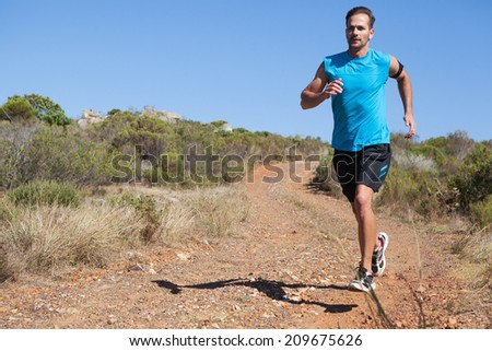 Athletic man jogging on country trail on a sunny day - stock photo