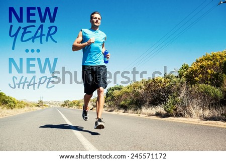 Athletic man jogging on open road holding bottle against new year new shape - stock photo