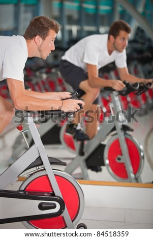 Athletic man on excercise bike at the gym - stock photo
