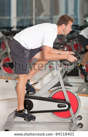 Athletic man on excercise bike at the gym