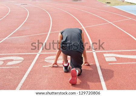 Athletic man on track starting to run - stock photo