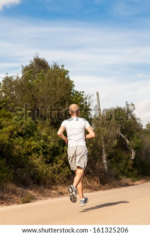 athletic man runner jogging in nature outdoor fitness summer healthy
