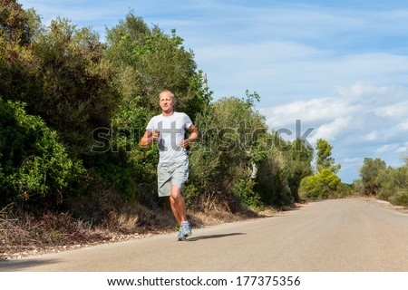 athletic man runner jogging in nature outdoor summer - stock photo