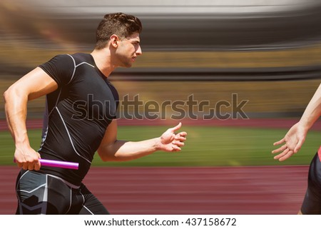 Athletic man running a relays against athletic track in a stadium - stock photo