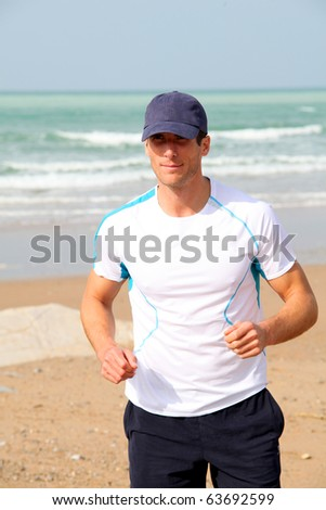 Athletic man running by the sea in summer - stock photo