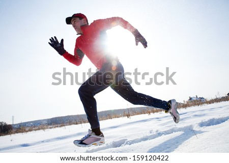 Athletic  man running in winter day on snow - stock photo