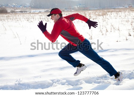Athletic  man running in winter day on snow road - stock photo