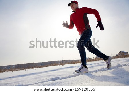 Athletic  man running in winter day on snow road