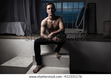 Athletic man sitting in a dark room - stock photo