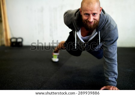 Athletic man smiling at camera while doing a one arm pushup