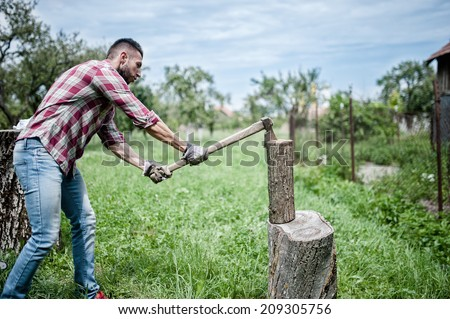 athletic man splitting wood and cutting firewood with axe  - stock photo