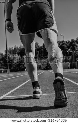 Athletic man starting evening jogging in sun rays - stock photo