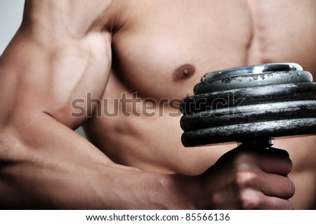 Athletic man with six-pack abs and weight - stock photo