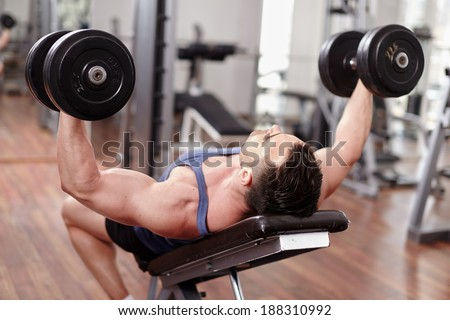Athletic man working out his chest with dumbbells on a bench press - stock photo