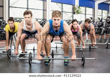 Athletic men and women working out at crossfit gym - stock photo